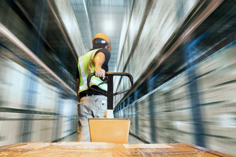 Warehouse worker pulling a hand pallet